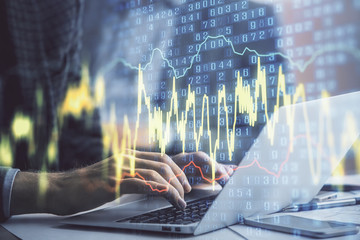 Double exposure of market chart with man working on computer on background. Concept of financial...