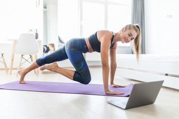 Attractive sportswoman with laptop doing push ups at home. Wall mural