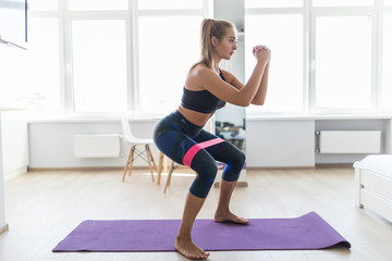 Young woman during her fitness workout at home with rubber resistance band Fotomurales