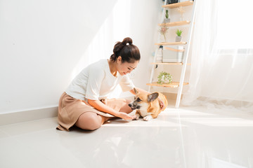 Cheerful Asian woman playing with her Corgi dog