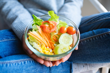 Closeup image of a woman holding a bowl of fresh mixed vegetables salad in hands
