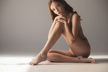 sensual girl in lingerie looking at camera while sitting on grey background with sunlight