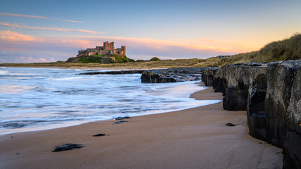 Small Cliffs at Bamburgh Beach, and dunes which are dominated by the imposing medieval castle and located within Northumberland Coast Area of Outstanding Natural Beauty
