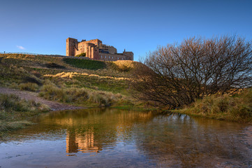 Floodwater in Bamburgh Beach Dunes, which are dominated by the imposing medieval castle and located within Northumberland Coast Area of Outstanding Natural Beauty