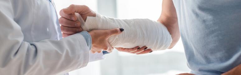 panoramic shot of orthopedist touching injured hand of man