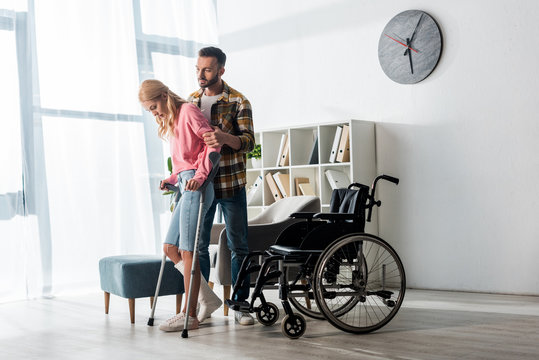 wheelchair near injured woman holding crutches while standing with man