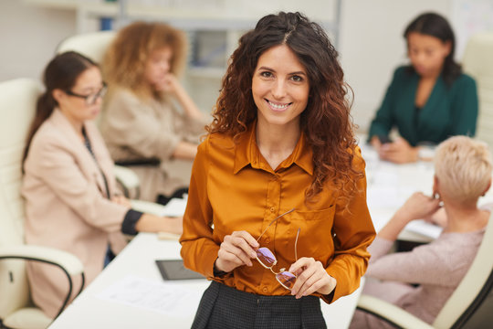 Charming Caucasian woman standing with with eyeglasses taken off looking at camera smiling with colleagues coworking behind her medium portrait