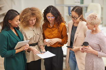 Group of five women talking about work during coffee break standing together in office room