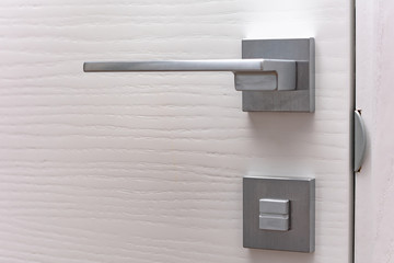 Modern chrome door handle and lock on white wooden door. Close-up elements of the modern interior of the apartment. Ajar white door. Wall mural