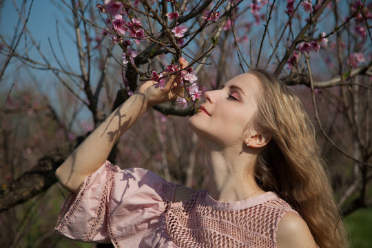 Beautiful blonde woman in pink dress walks through the flowering garden spring