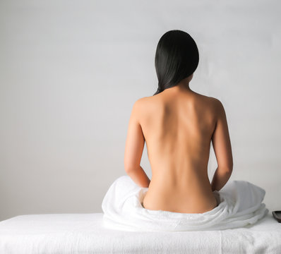 Back view of Asian female sitting on bed waiting for spa massage