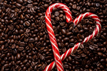 Poster Café en grains background of roasted coffee beans. A heart made of a Christmas cane. Sweet lollipops