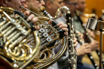 Detail of orchestra, philharmoic player playing on french-horn during huge philharmonic concert (shallow DOF)
