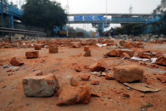 Pieces of bricks lay scattered on a road during a protest against a new citizenship law, in New Delhi