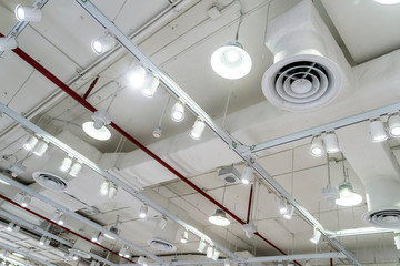Bare ceiling with air duct, CCTV, air conditioner pipe and fire sprinkler system on white ceiling wall. Air flow and ventilation system. Ceiling lamp light with opened light. Interior architecture.