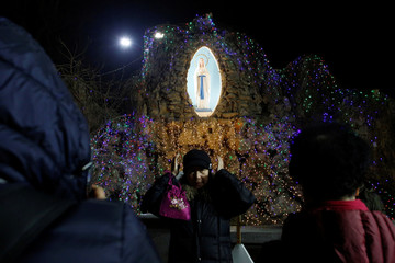 Woman adjusts her hat as she poses for pictures in front of a Virgin Mary statue at Xishiku Cathedral on Christmas Eve in Beijing