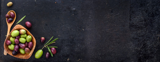 Top view of organic olive fruit on rustic black background.