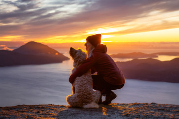 Foto auf Leinwand Braun Adventurous Girl Hiking on top of a Mountain with a dog during a colorful sunset. Taken on Tunnel Bluffs Hike, near Vancouver and Squamish, British Columbia, Canada.