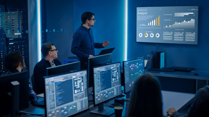Team of Professional IT Developers Have a Meeting, Speaker Shows Growth Data with Graphs, Charts, Software UI. Shown on TV. Concept: Software UI Development, Deep Learning, Graphs, Charts.