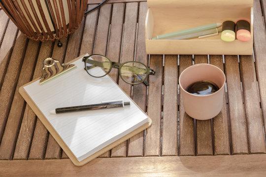 Bureau en bois avec un café dans une tasse rose une paire de lunettes - bureau écologique avec un bloc-note en bois et du papier recyclé une trousse en bois recyclé et une lampe en osier tressé