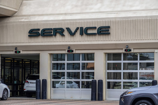 White cars entering an automobile service center garage through an open garage door. Two other doors are closed