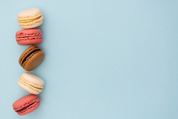 Macarons cakes. Fashion or feminine background delicious macaroons in row on blue background. Flat lay social media walpaper. Copy space.