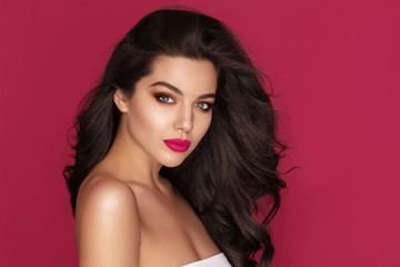 Beautiful Brunette Woman Portrait with brown eyes and Healthy Long Shiny Wavy black hair. Volume shampoo. Attractive Beauty model with professional make up against pink background Wall mural