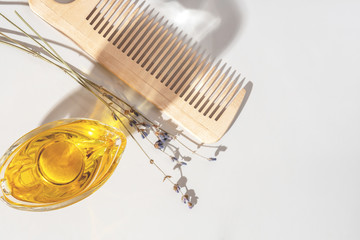 Oil, wooden comb and dry lavender on a light background, top view, flat lay. Natural cosmetics for hair care. Hair care spa concept. Homemade organic cosmetics. Minimal, stylish, trend concept.
