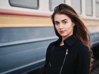 Young beautiful brown haired woman in black jacket blue skirt with gorgeous long legs in vintage beret emotionally posing on railway station train background with cinematic color grading