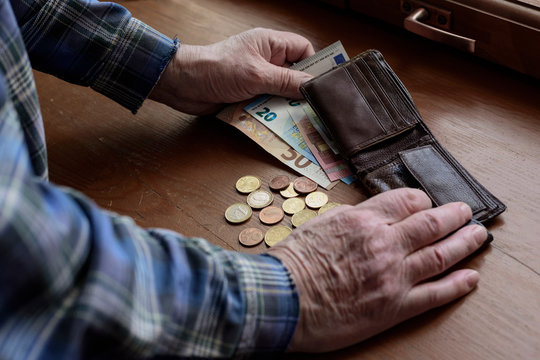 The hands of an old man and counting money, euros. The concept of poverty, low income, austerity in old age.