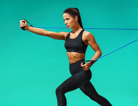 Strong woman using resistance band in her exercise routine. Photo of fitness model workout on turquoise background. Strength and motivation
