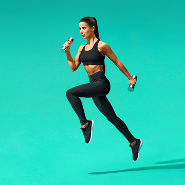 Sporty woman jumping with dumbbells. Photo of active woman in black sportswear on turquoise background. Dynamic movement. Side view. Sport and healthy lifestyle