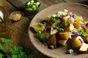 Potato salad with Dijon dressing, with parsley, olive oil, mustard seeds, red and green onions close-up. Wooden background, horizontal arrangement.