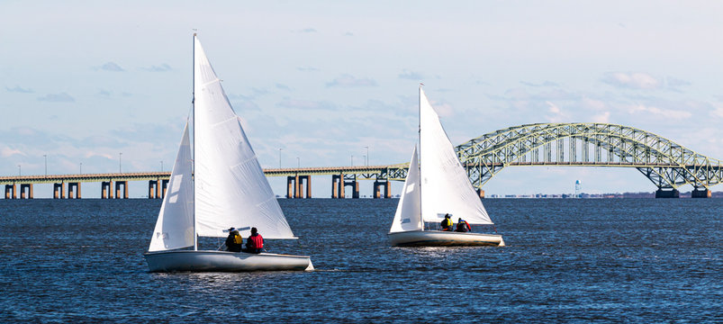 Two two person sailboats sailing toward West Islip with the Great South Bay bridge