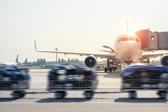 Luggage motion blurred trolley cart going fast delivering passenger baggage to modern plane on taxiway at airport on bright sunny day. Commercial aircraft on background at sunset or sunrise time