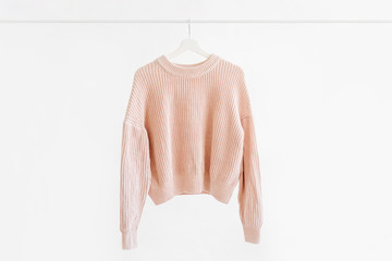 Feminine pale pink warm sweater on hanger on white background. Elegant  jumper  fashion outfit. Spring wardrobe. Minimal concept.