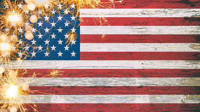 Happy 4th of July - American flag on wooden rustic vintage texture with sparklers and firework