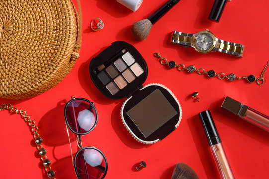 Women's accessories and background for girls. Women bag, watches, and cosmetics. Red background, styling photography and creative light.