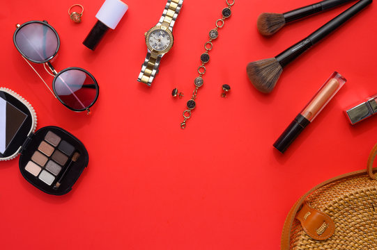 Blogging Beauty Concept.Professional female makeup accessories, watches, bracelet, sunglasses and a fashionable bag on a red backgroundFemale background and fashion.Instagram, women's stuff.Creative