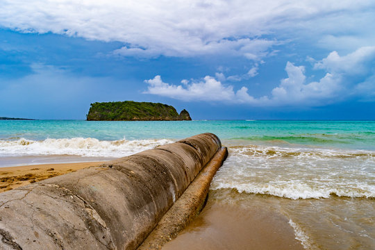 Cylindrical cement grey water/ storm water/ sewage/ sewer pipe outlet above ground from sea shore into the ocean. Old dirty exposed waste water irrigation management pipeline drainage on beach coast.