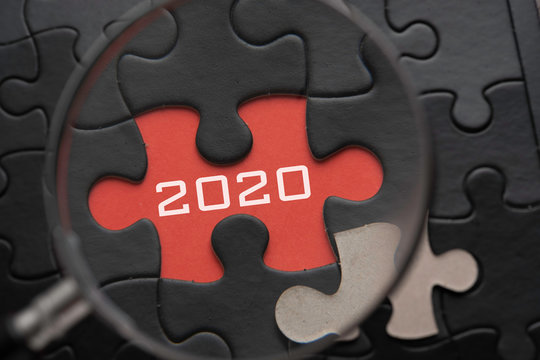 Magnifying glass focus on puzzle written 2020.