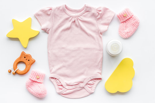 Pink bodysuit for baby girl near children's things on white background top-down