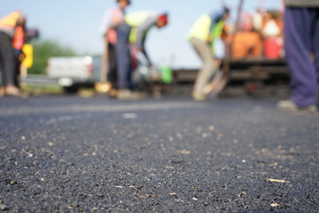 Construction workers on the asphalt road, blurred pictures