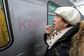 A participant of a welcoming ceremony puts on lipstick upon the arrival of the first direct train from Saint Petersburg in Sevastopol