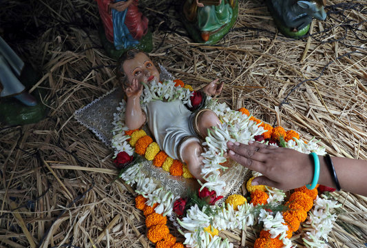 A worshipper touches a figure of the baby Jesus at a church during Christmas celebrations in Kolkata