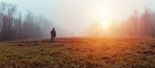 Papiers peints Beige Panoramic view young man standing in jakcket and pants with backpack on meadow and trees with sun