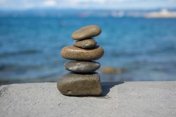Spoed Foto op Canvas Zen Five stones cairn tower, rock zen sculpture, brown beige pebbles and sea light blue background