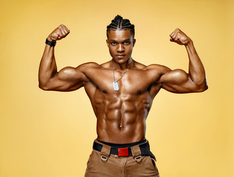 Athletic man posing. Photo of man with perfect physique on yellow background. Strength and motivation