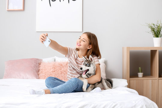 Cute teenage girl with funny husky puppy taking selfie on bed at home