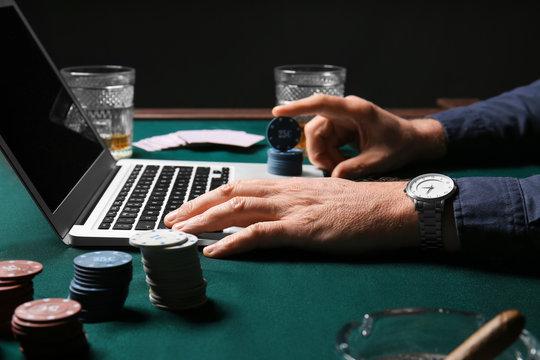 Mature businessman playing poker online, closeup